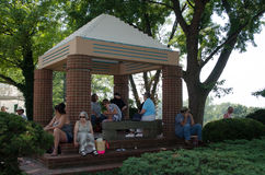 A resting place. A various mixed group of people, take time to sit and rest at this shaded pavilion on a hot day in Michigan stock image