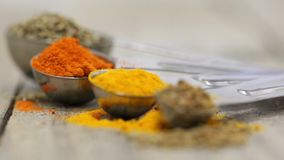 Various mixed spices oregano, curcuma, paprika, anise in metal scoops on wooden table stock footage