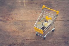 Various money coins Bath in yellow mini shopping cart or supermarket trolley set on wooden floor. Stock Photos