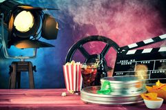 Cinematography film theme with refreshments. Various movie and film props including a clapperboard alongside popcorn, tickets and refreshments in a stock images