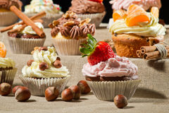 Various muffins with cream, fruits and nuts Royalty Free Stock Photos