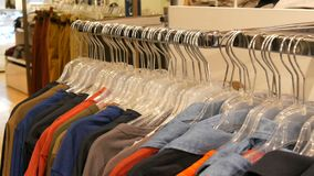 Various multi-colored clothing hanging on hangers in a clothing store in mall or shopping center. Various multi-colored clothing hanging on hangers in a clothing stock footage