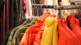 Various multi-colored warm women`s clothing hanging on hangers in a clothing store in mall or shopping center. Various multi-colored warm women`s clothing stock video footage