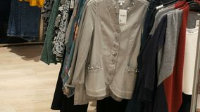 Various multi-colored women`s clothing hanging on hangers in a clothing store in mall or shopping center. Various multi-colored women`s clothing hanging on stock footage
