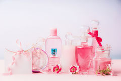 Various natural cosmetic products in bottles and jars with pink flowers at pastel background, front view. Beauty and skin care con Stock Images