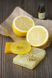 Various natural soaps. Lemon and bottle of oil on rustic wooden background Stock Image