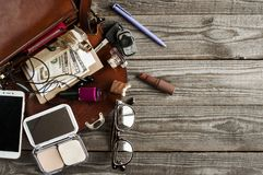 Various necessary accessories in a women`s handbag. For urban life, flat lay on wooden background. free space for text Royalty Free Stock Photography