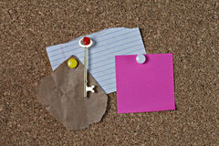 Various notes and key on corkboard Royalty Free Stock Images