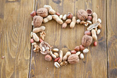 Various nuts arranged in a heart shape Stock Photos