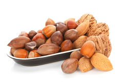 Various nuts in bowl on white. Royalty Free Stock Photo