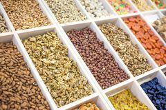 Various nuts and dried fruits on the market: hazelnuts, almonds, peanuts, cashews, raisins, candied fruits, dried fruits, prunes stock photos