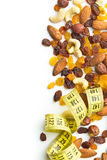 Various nuts and raisins with measuring tape. Royalty Free Stock Image