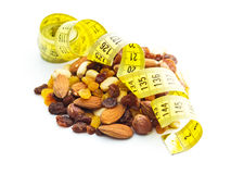 Various nuts and raisins with measuring tape. Stock Photography