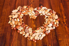 Various nuts stacked in shape heart on background dark wood. Stock Photography