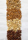 Various nuts on white wooden table. Cashew, hazelnuts, walnuts, almonds. Top view, flat lay. Closeup.  royalty free stock photos