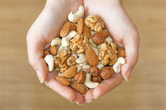 Various nuts in hands Royalty Free Stock Images