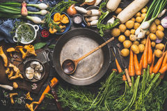 Various organic vegetables ingredients around empty aged cooking pot with wooden spoon on old kitchen table Royalty Free Stock Images
