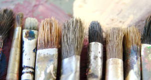 Various paint brushes on table. Close-up of various paint brushes on table stock video