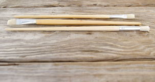 Various paint brushes on wooden table. Close-up of various paint brushes on wooden table stock footage