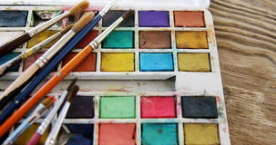 Various paint brushes on wooden table. Close-up of various paint brushes on wooden table stock video footage