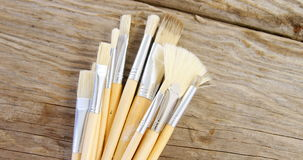 Various paint brushes on wooden table stock footage