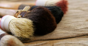 Various paint brushes on wooden table stock video footage