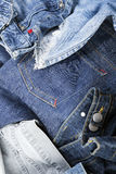 Jeans Background. Various pairs of jeans pants scattered in chaos Stock Photos
