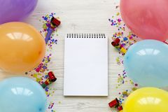 Various party balloons, confetti and blank notepad. Decoration party concept.