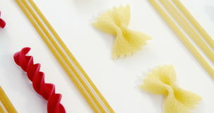 Various pasta arranged on white background stock footage