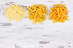 Various pasta as ingredients containing carbohydrates and dietary fiber, healthy nutrition, copy space for text. Various pasta as ingredients containing stock images