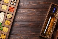 Various pasta in wooden box and wine. Various pasta in wooden box and white wine bottle. Cooking concept. Top view with space for your text Royalty Free Stock Images