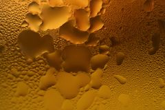 Various patterns of condensation on the glass full of amber color chilled beer. Texture Background stock photo