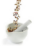 Various peppercorns falling into mortar and pestle Stock Photography
