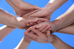 Various persons holding hands. In front of bright blue sky Royalty Free Stock Photos
