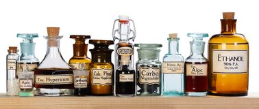 Various pharmacy bottles of homeopathic medicine. On wooden board stock photo