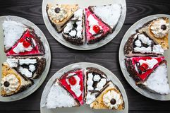 Various pieces of cake on plates on dark wood background royalty free stock images