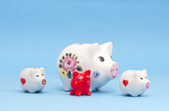 Various piggy-banks on azure background Stock Photos