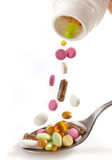 Various pills falling into spoon Stock Photos