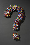 Various pills forming question mark on black background Royalty Free Stock Image