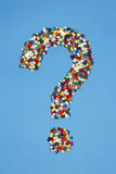 Various pills forming question mark on blue background Royalty Free Stock Photo