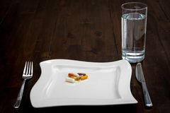 Various pills are on white plates next to a glass of water on a brown table royalty free stock photo
