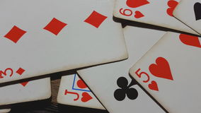 Various playing cards rotate on table. stock footage