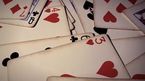 Various playing cards rotate on table. Macro shot stock footage