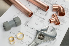 Various Plumbers Tools and Plumbing Materials on Architectural H. Various plumbers tools and plumbing materials including copper pipe, elbow joint, wrench and Royalty Free Stock Images