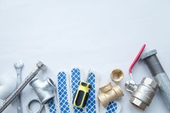 Various plumbers tools. And plumbing materials including stainless steel, plastic and copper pipe, elbow joint, wrench and spanner. White background. Top view royalty free stock photos