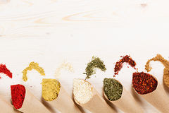 Various powder spices close-up in paper corner on white wooden board with copy space. Royalty Free Stock Images