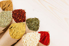 Various powder spices close-up in paper corner on white wooden board with copy space. Stock Image