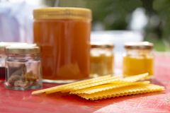 Various products such as propolis, honey wax plates against blurred background stock photos