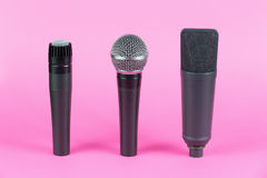 Various professional microphones on pink background Stock Image