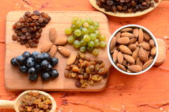 Various raisins, vine berries and almonds on chopping board Stock Image